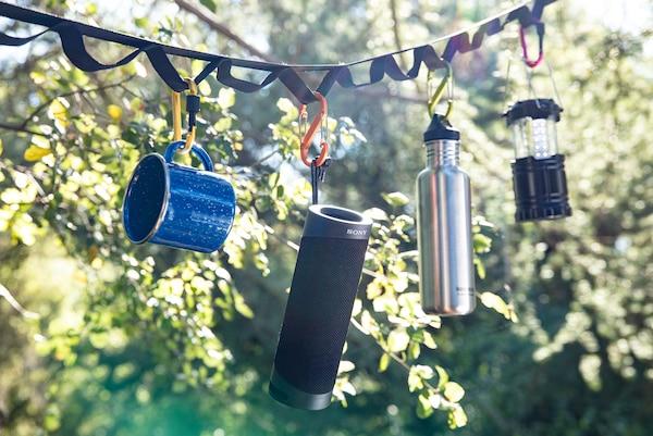 Głośnik SRS-XB23 wiszący na taśmie rozpiętej wśród drzew