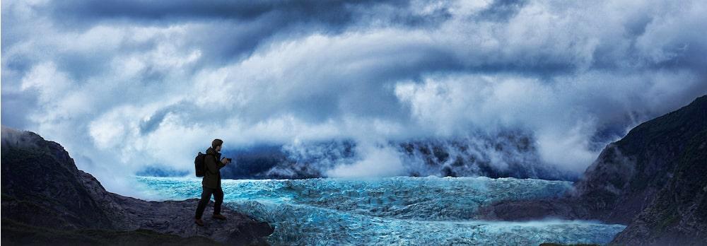 Zdęcie przedstawiające użytkownika trzymającego aparat wdzikiej scenerii górskiej zmgłą, chmurami ipolem lodowym